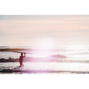 magic hour as cold water surfer heads into ocean